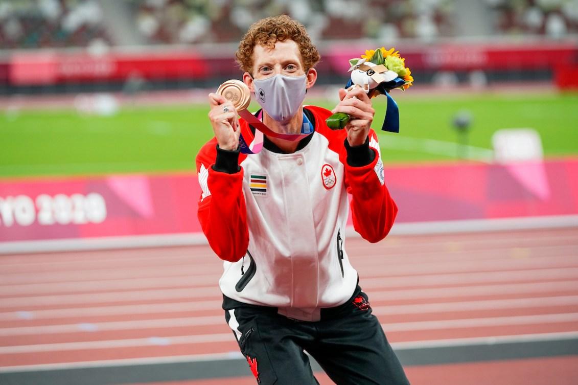 Evan Dunfee celebrates Olympic bronze on the podium.