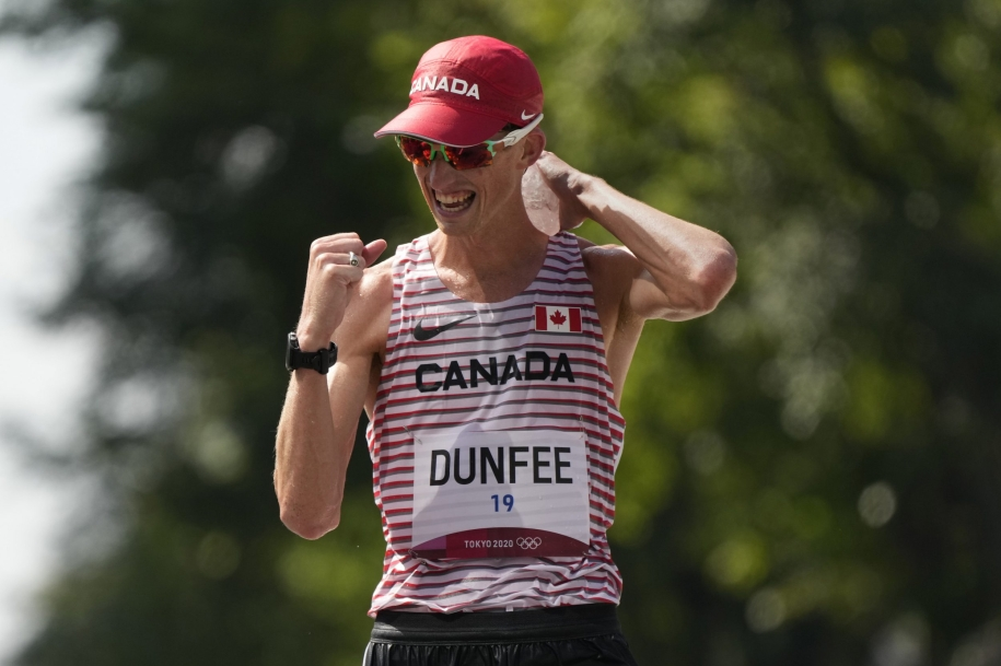 Evan Dunfee pumps his fist in celebration as he wins bronze in the 50km race walk