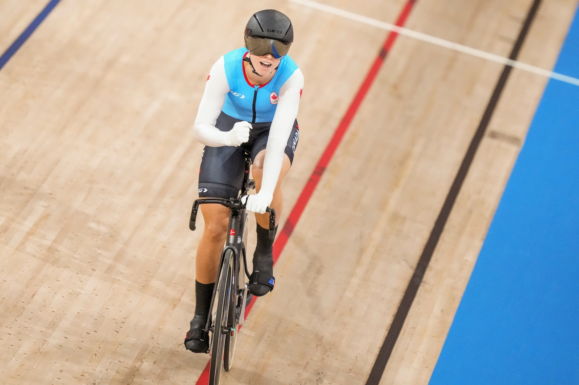 Kelsey Mitchell pumps her fist after winning her heat in track cycling