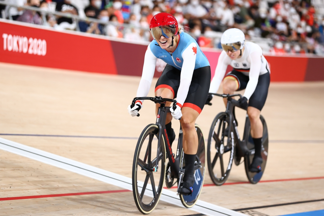 Kelsey Mitchell in front of German racer as they cross finish line in track cycling sprint