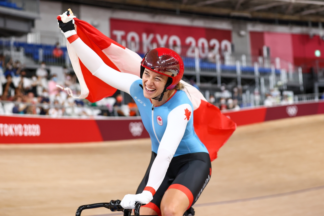 Kelsey Mitchell waves the Canadian flag while doing a victory lap at the velodrome