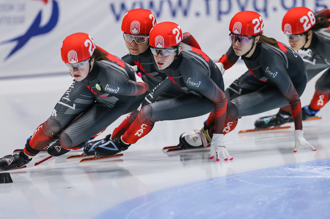 Short track speed skaters racing in a pack