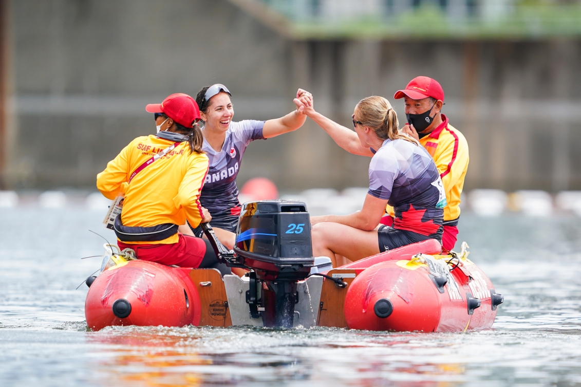 Laurence Vincent Lapointe and Katie Vincent hold hands on a rescue boat after falling in the water in celebration