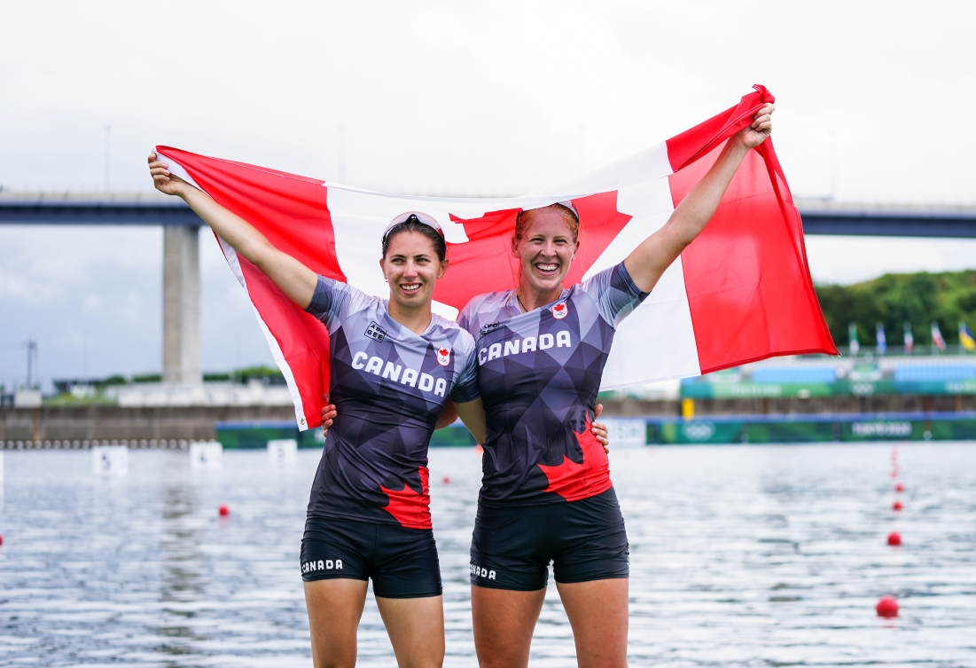 Laurence Vincent Lapointe and Katie Vincent pose with the Canadian flag