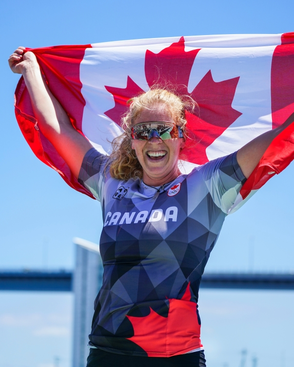 Laurence Vincent Lapointe holds the Canadian flag above her head