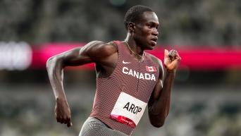 A mid shot of Marco Arop running during a race. His right arm is bent and behind him, his left arm is in front, by his chest.
