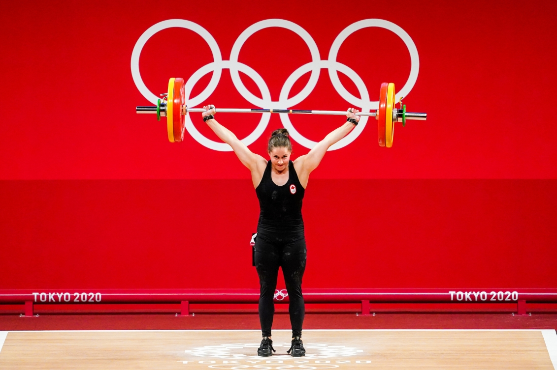 Maude Charron with the bar bell lifted above her head