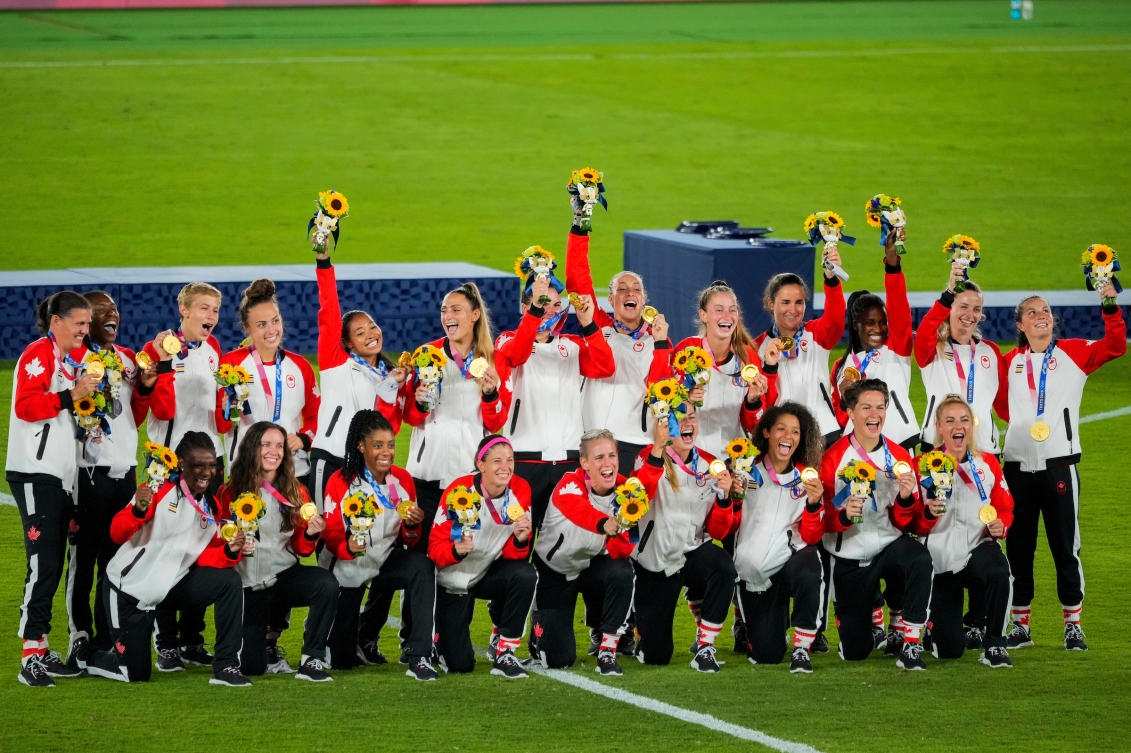 Women's soccer team pose with medals after victory ceremony