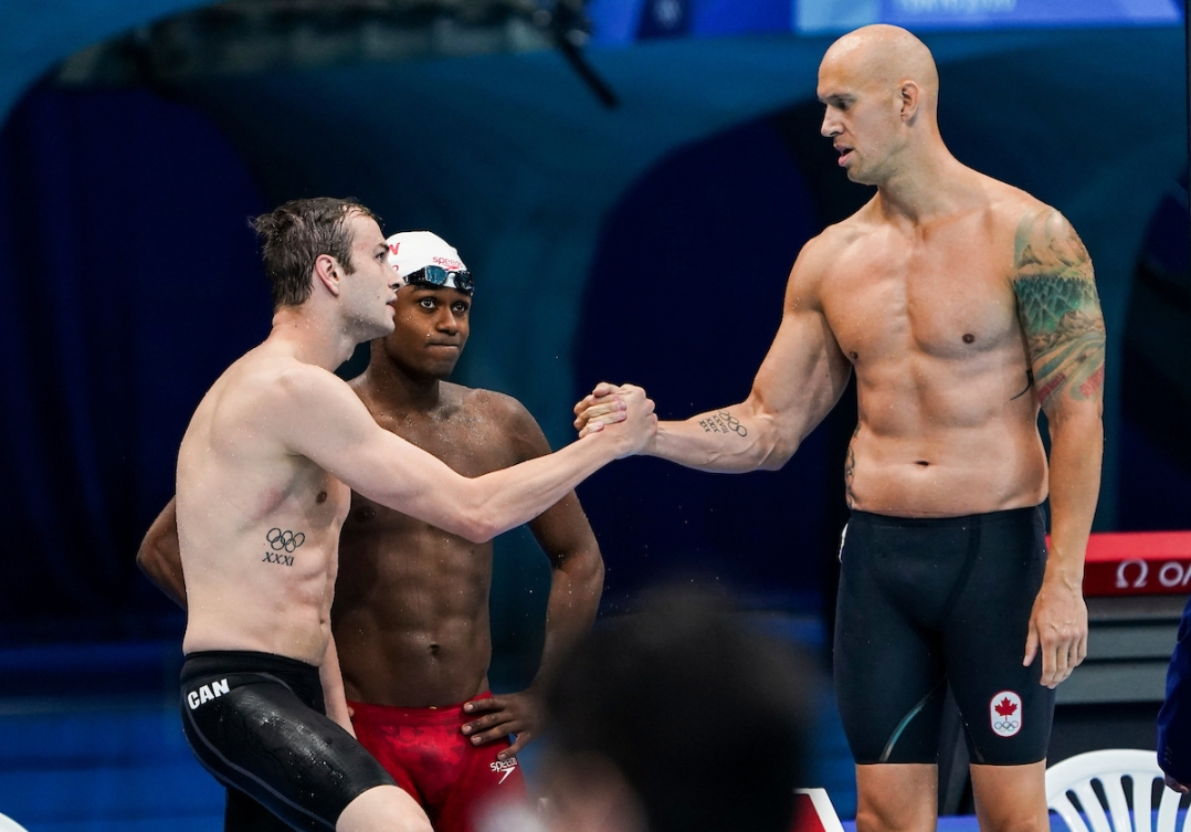 Three male Canadian swimmers stand on the pool deck