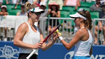 Gabriela Dabrowski (left) chats with doubles parter Luisa Stefani as they exchange tennis balls.