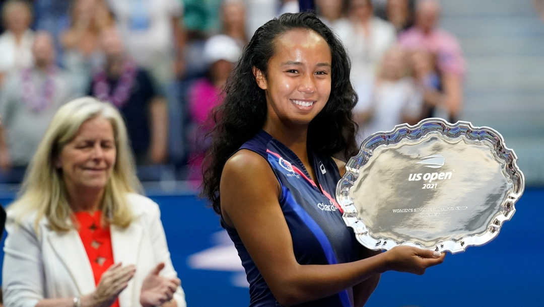 Leylah Fernandez, of Canada, holds up the runner-up trophy (shaped like a silver plate with scalloped edges). The light is reflecting off the plate onto her face.