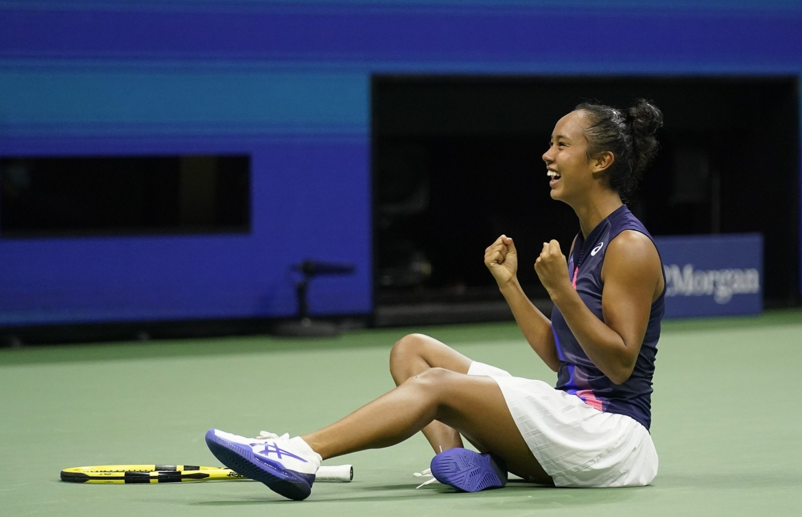 Leylah Fernandez pumps her fists while sitting on the court in celebration after a win