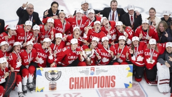 Canadian women's hockey team poses with the sign about being 2021 World Champions