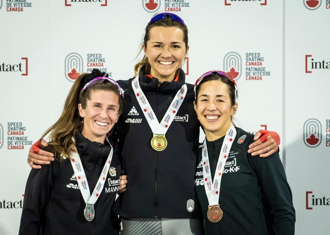 Isabelle Weidemann, Ivanie Blondin and Valerie Maltais stand on the podium with medals around neck