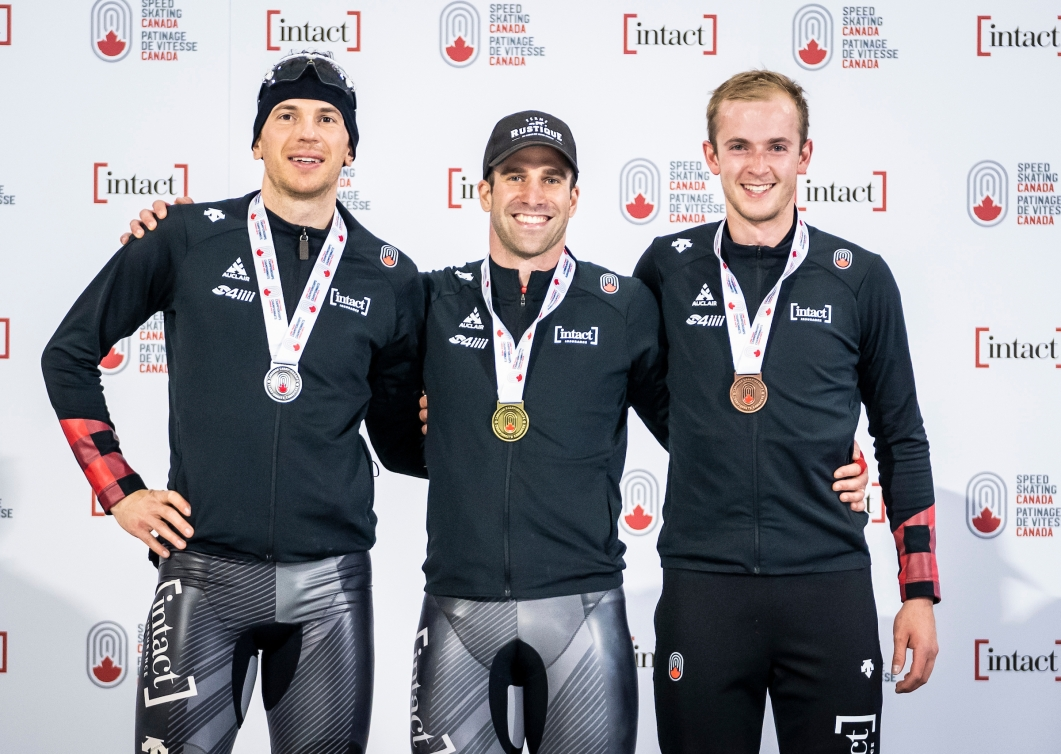 Three male speed skaters stand on a podium