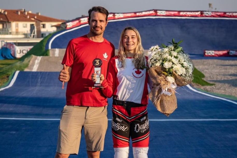 Adam Muys gives the thumbs up and Molly Simpson poses with a bronze medal and flower bouquet on the race track.