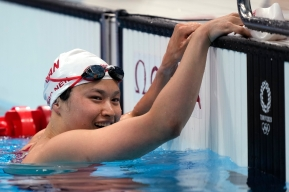 Maggie Mac Neil rests her hands on the pool deck and smiles after winning the women's 100m race at Tokyo 2020.
