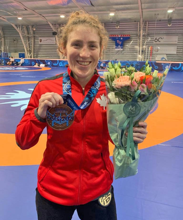 Samantha Stewart wears her bronze medal around her neck and holds it up with her right hand while holding flowers in her left hand.