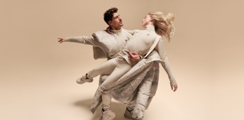Piper Gilles and Paul Poirier perform a lift while wearing white pants and tops