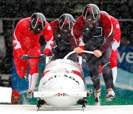 Lyndon Rush, Chris LeBihan, Dave Bissett et Lascelles Brown poussant le bobsleigh