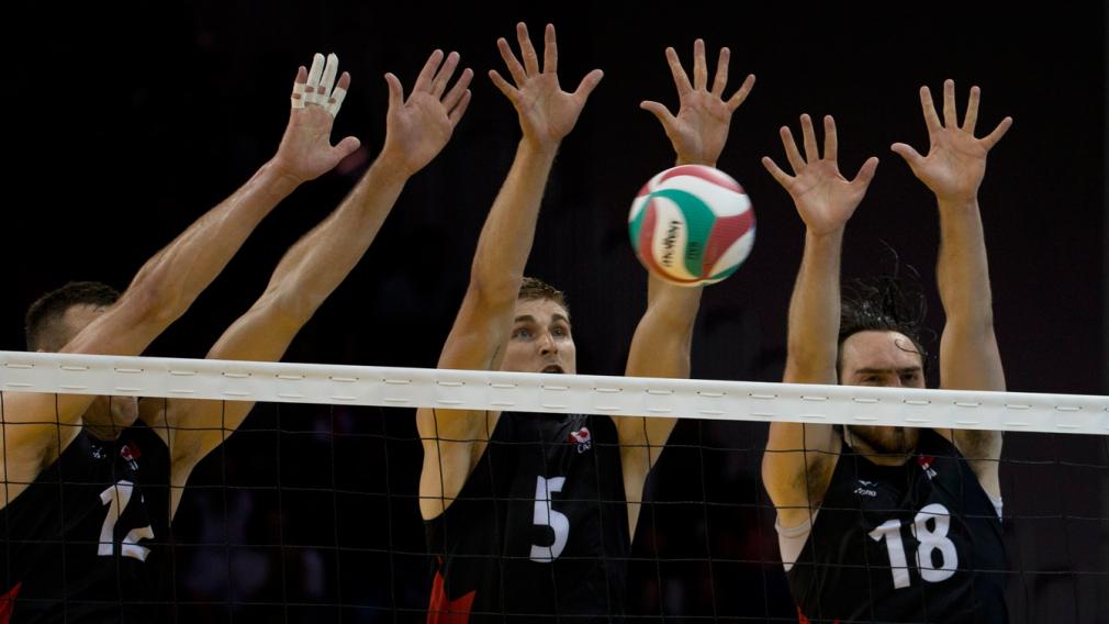 Trois joueurs canadiens tentent de bloquer un smash au volleyball