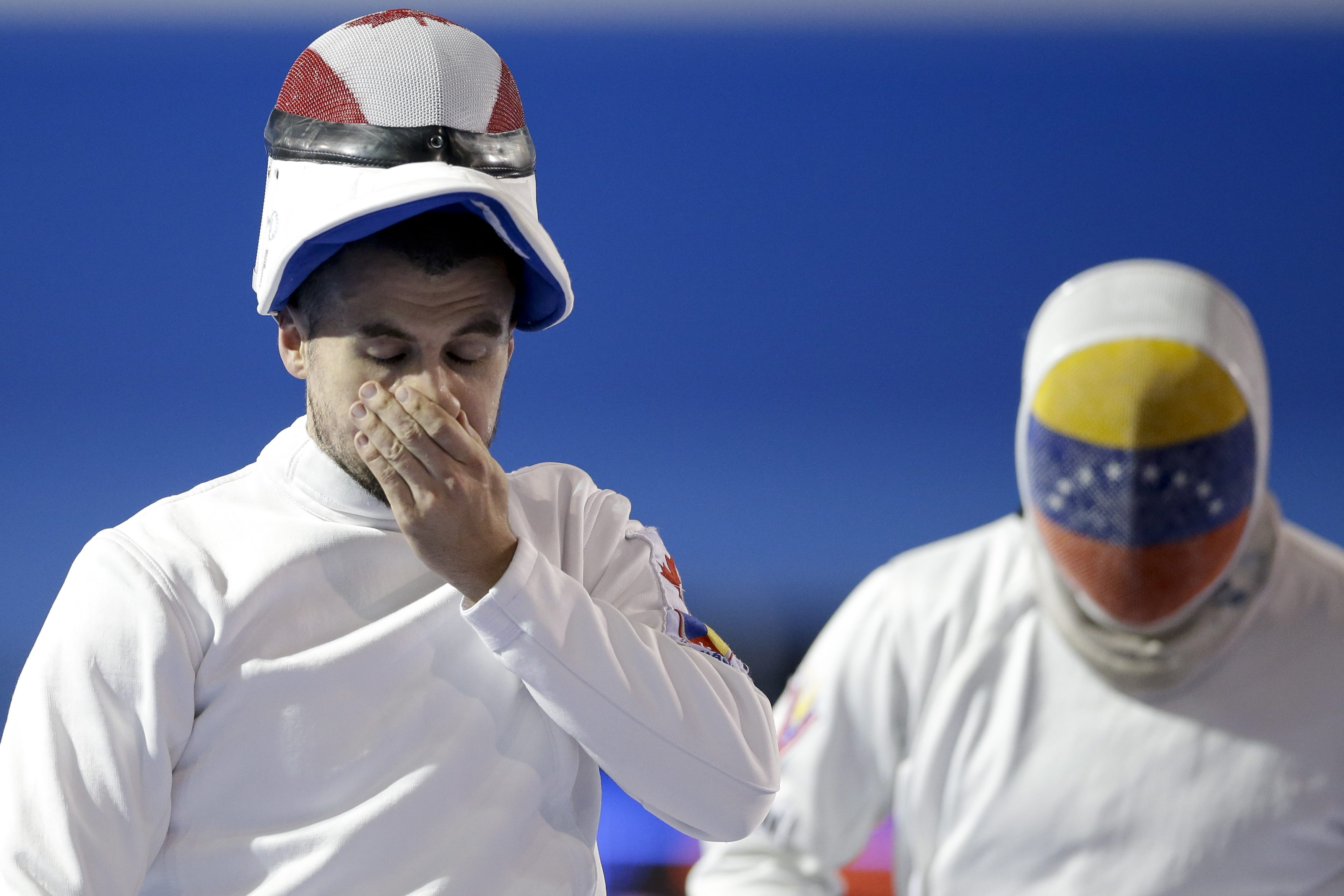 Canada's Maxime Brinck-Croteau, left, reacts during his epee bout against Venezuela's Ruben Limardo, right, in fencing competition in the Pan Am Games in Toronto Tuesday, July 21, 2015. Limardo won, 15-0. (AP Photo/Gregory Bull)