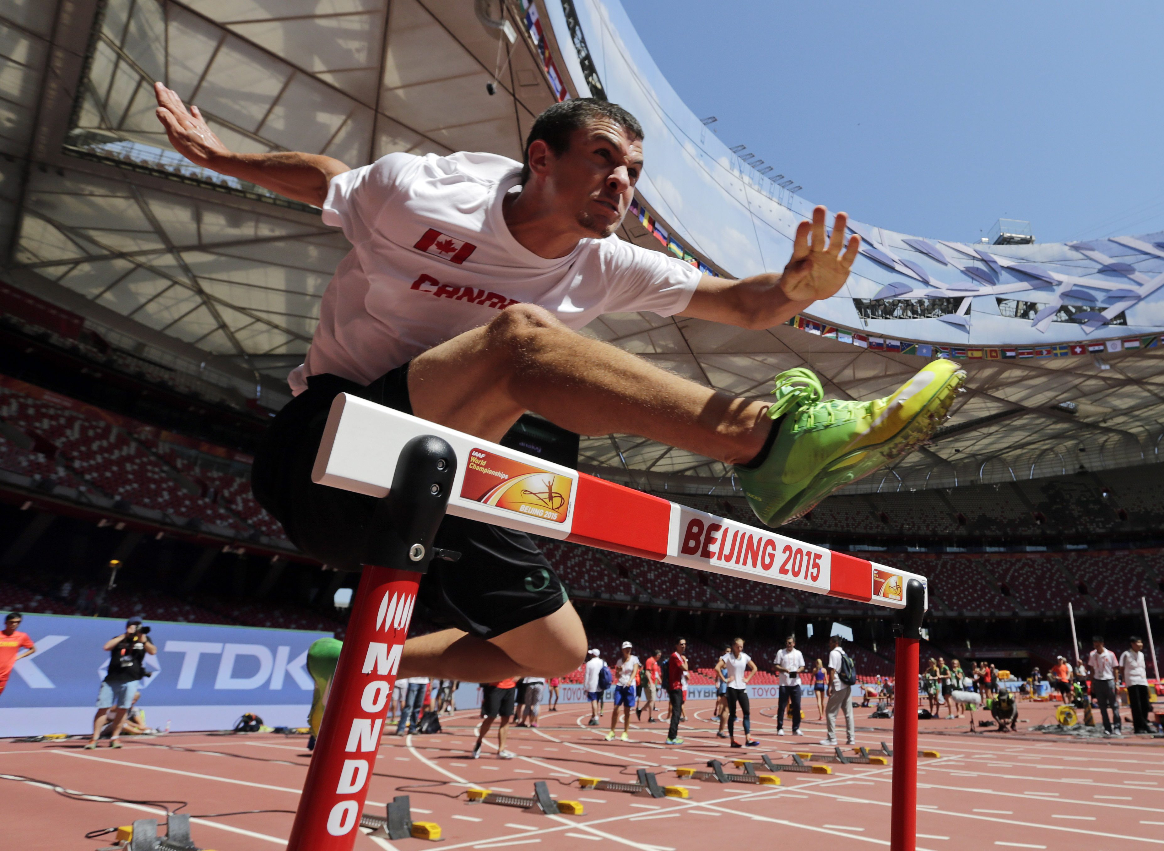 Canada's Johnathan Cabral clears a hurdle during a training session before the World Athletic Championships at the Bird's Nest stadium in Beijing, Friday, Aug. 21, 2015. (AP Photo/Andy Wong)