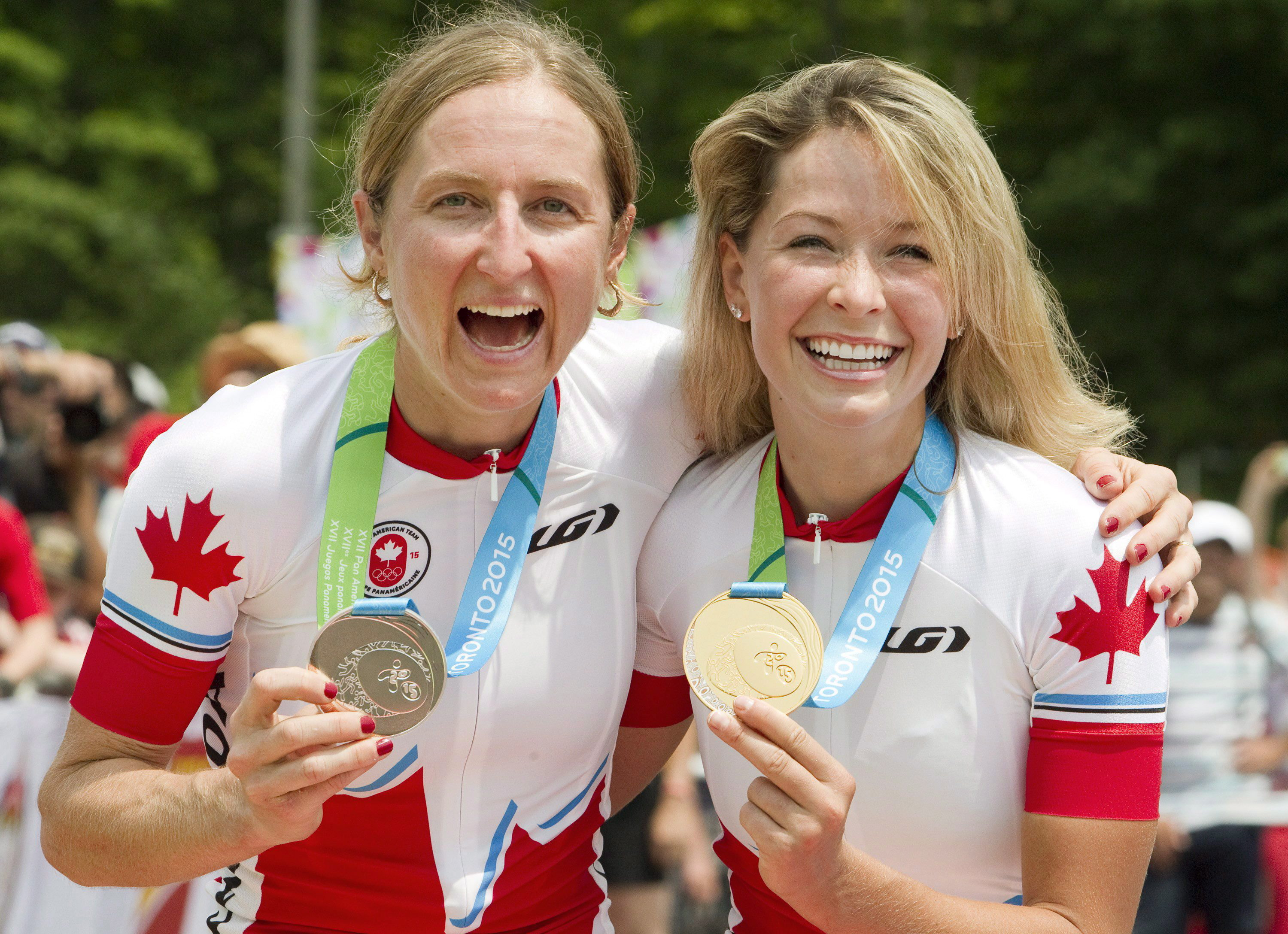Canadians Catharine Pendrel, right, and Emily Batty with their silver and gold medals at the Hardwood Mountain Bike Park in Oro-Medonte, Ont., where they finished second and first, respectively in the women's mountain bike event at the Toronto 2015 Pan Am Games on Sunday, July 12, 2015. THE CANADIAN PRESS/Fred Thornhill
