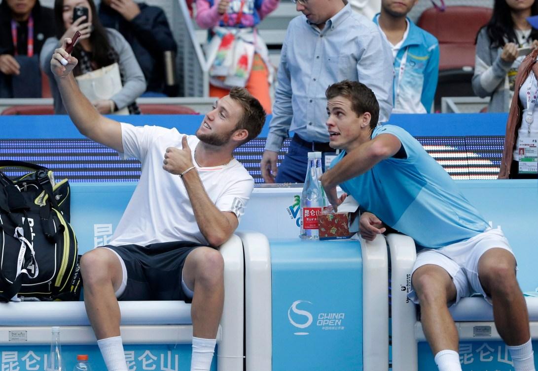 Jack Sock et Vasek Pospisil prennent un selfie après avoir défait Daniel Nestor et Edouard Roger-Vasselin en finale du tournoi China Open à Beijing, le 11 octobre 2015. (AP Photo/Andy Wong)
