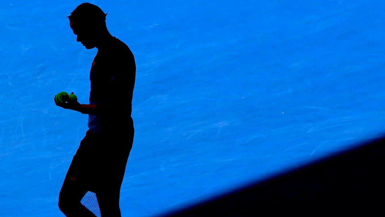 Dans l'ombre du soleil d'après-midi, Raonic s'apprête à servir contre Viktor Troicki au troisième tour des Internationaux d'Australie le 23 janvier 2016.