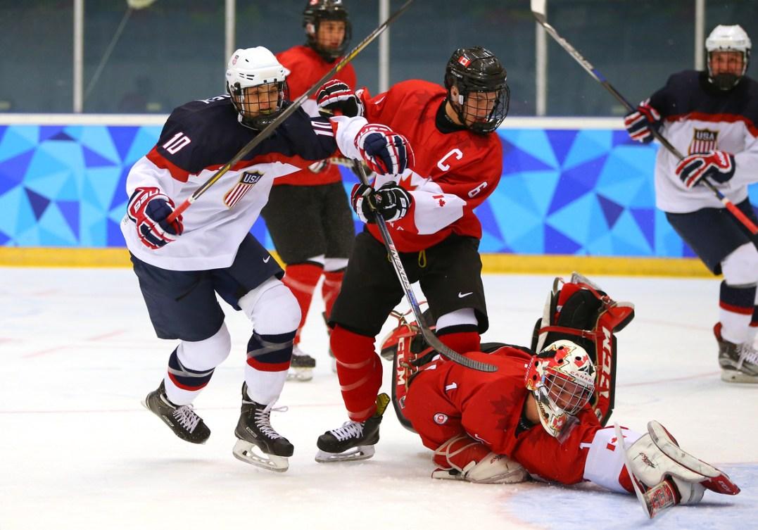 Le Canadien Alexis Gravel (à droite) ne peut arrêter le tir de TJ Walsh (absent de la photo) sous les yeux de l'Américain Jonathan Gruden (à gauche) pendant la finale du tournoi masculin de hockey sur glace opposant le Canada et les États-Unis à l'aréna Kristins lors des Jeux olympiques de la jeunesse d'hiver à Lillehammer, en Norvège, le 21 février 2016. Photo : Al Tielemans pour YIS/CIO. Image fournée par YIS/CIO.