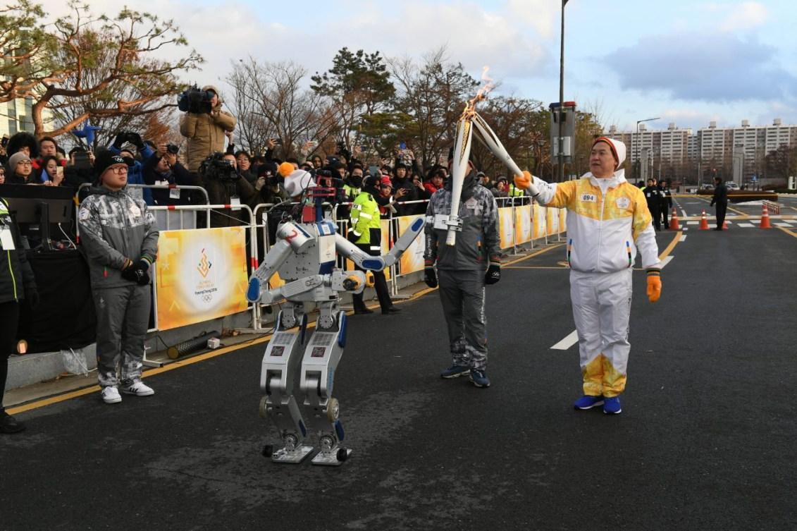 Un relayeur passe la flamme olympique à un robot