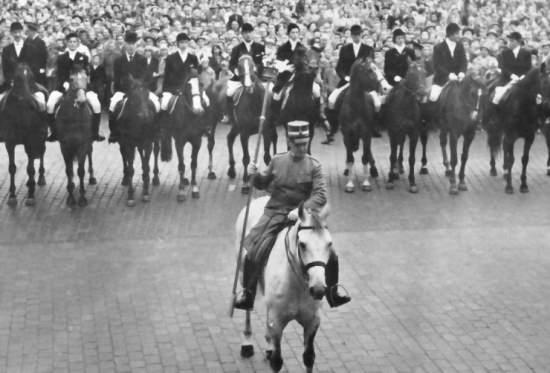 Un homme à cheval mène une rangée d'une dizaine de cavaliers à cheval.