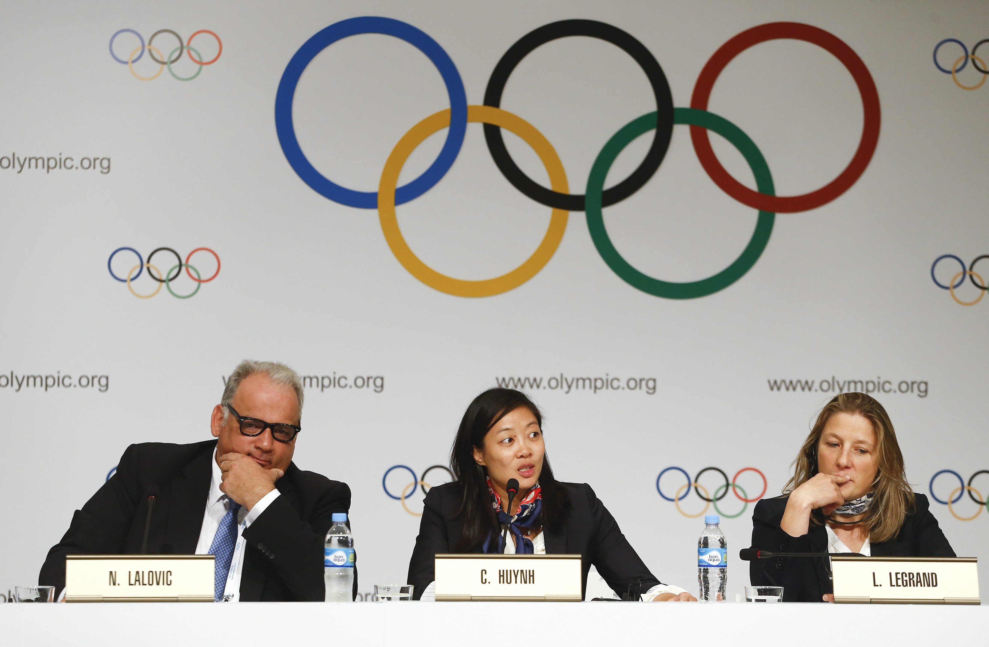 Canadian freestyle wrestler and olympic gold medalist Carol Huynh, center, speaks during a news conference in Buenos Aires, Argentina, Friday, Sept. 6, 2013. During the Sept. 4-10 International Olympic Committee (IOC) Executive Board meetings in Buenos Aires, members will vote on including one additional sport to the program of the 2020 and 2024 Games. Wrestling is up against squash and a combined baseball-softball bid. Huynh is flanked by Nenad Lalovic, head of the International Federation of Associated Wrestling Styles (FILA), left, and Lise Legrand, vice president of the French Wrestling Federation. (AP Photo/Victor R. Caivano)