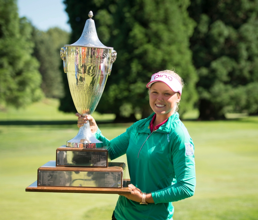 Brooke Henderson, of Canada, holds the championship trophy after winning the LPGA Cambia Portland Classic golf tournament Sunday, July 3, 2016, in Portland, Ore. (AP Photo/Troy Wayrynen)