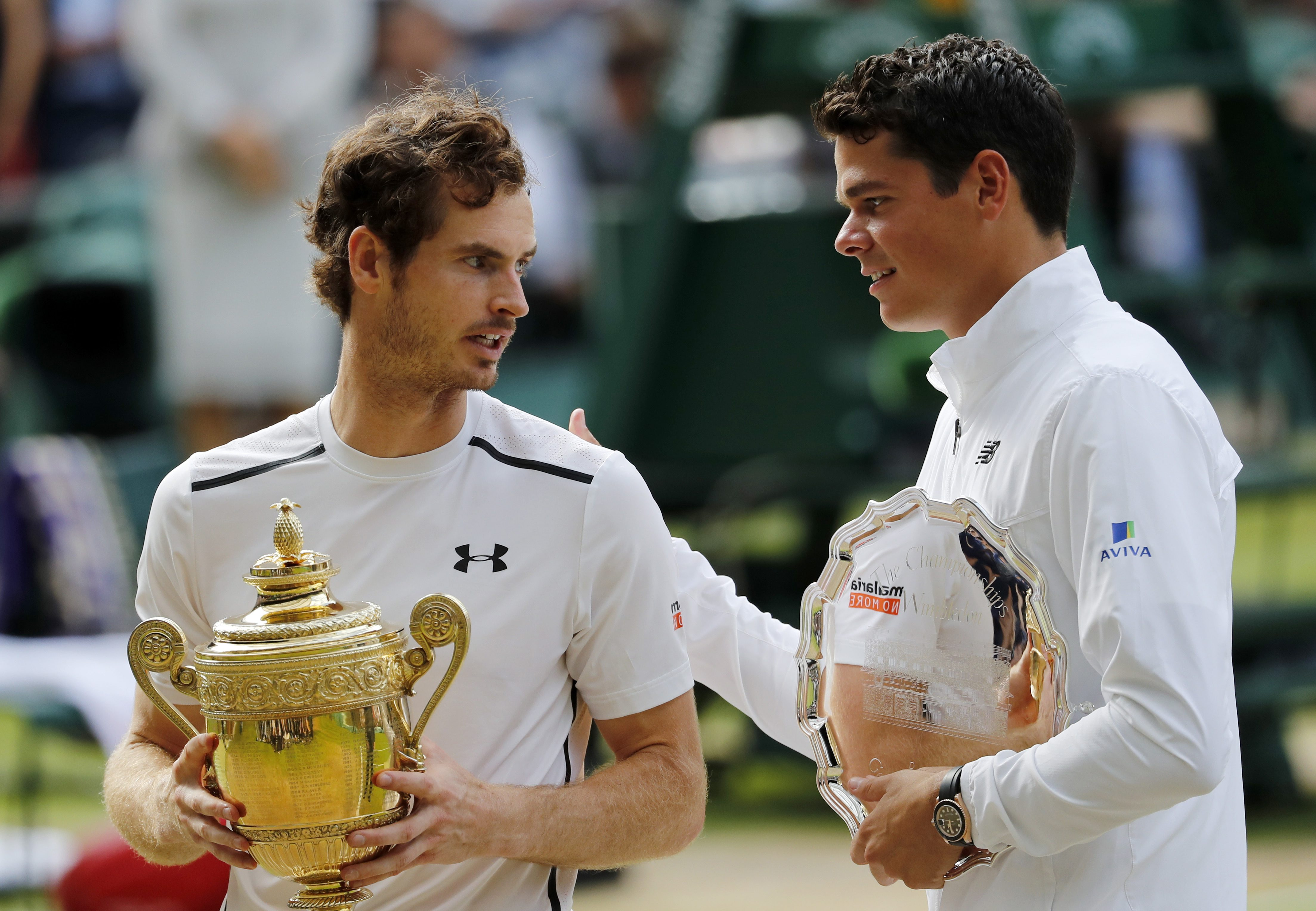 Andy Murray of Britain, left, holds up his trophy after beating Milos Raonic of Canada, right, in the men's singles final on day fourteen of the Wimbledon Tennis Championships in London, Sunday, July 10, 2016. (AP Photo/Ben Curtis)