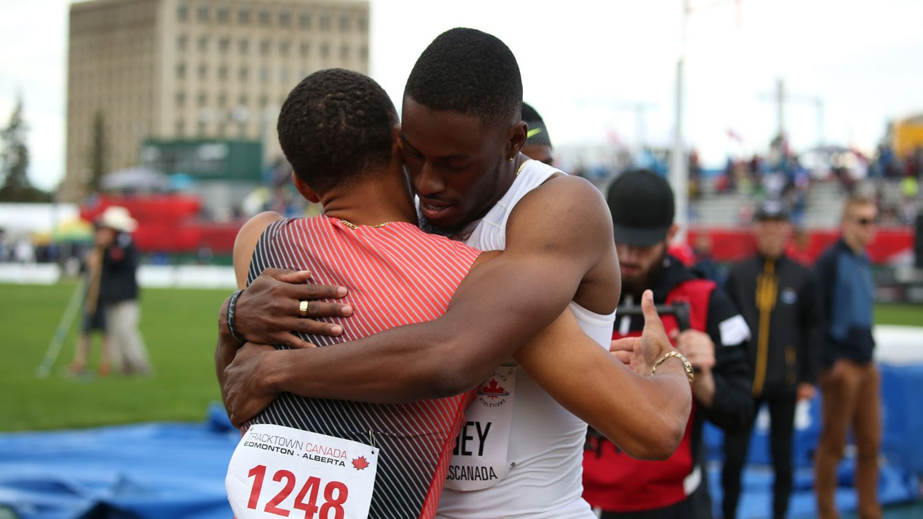 Accolade entre Andre De Grasse (en orange) et Brendon Rodney après la finale du 200 m aux Essais olympiques d'Athlétisme Canada, le 10 juillet 2016.