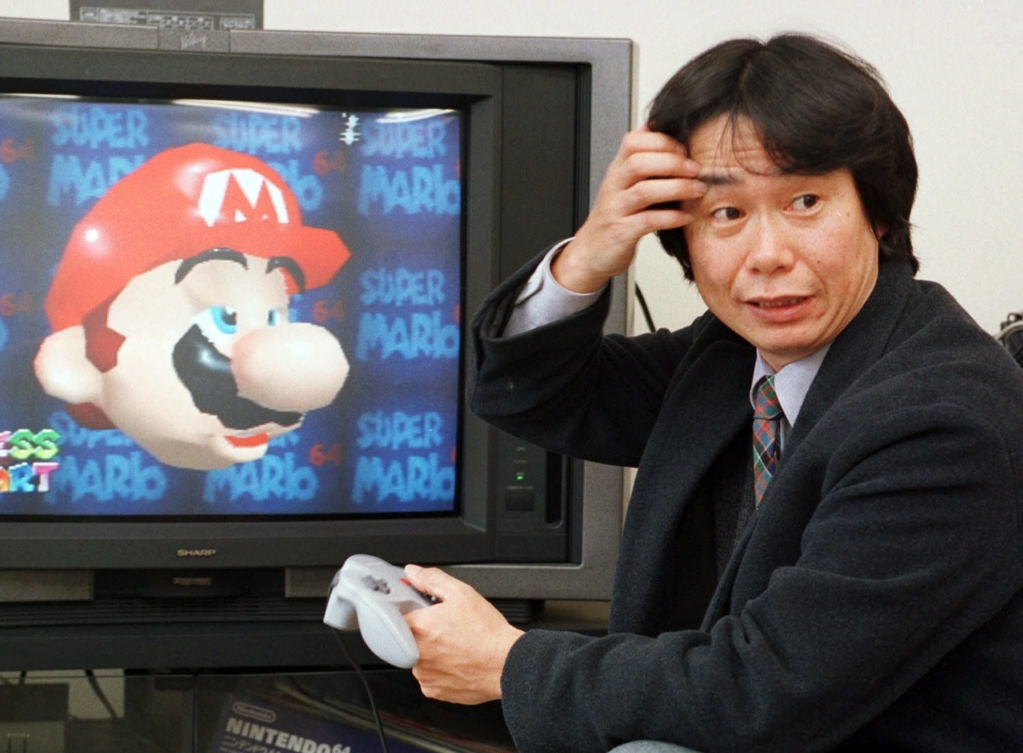 """FILE - In this Feb. 6, 1997 file photo, Shigeru Miyamoto, creator of Super Mario video game series, demonstrates Super Mario 64 in his office at the Nintendo Co. headquarters in Kyoto, Japan. Even though Mario hasn't changed much in nearly three decades, the latest game he stars in, the newly released """"The New Super Mario Bros. Wii,"""" is one of the holiday season's top titles. (AP Photo/Atsushi Tsukada)"""
