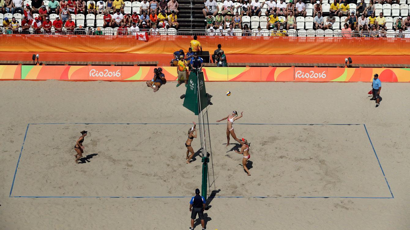 Sarah Pavan (au centre) effectue un smash contre Jamie Broder et Kristina Valjas (au filet) lors du match de quarts de finale opposant les deux équipes canadiennes au tournoi olympique féminin de volleyball de plage à Rio, le 13 août 2016. (Photo AP/Marcio Jose Sanchez)