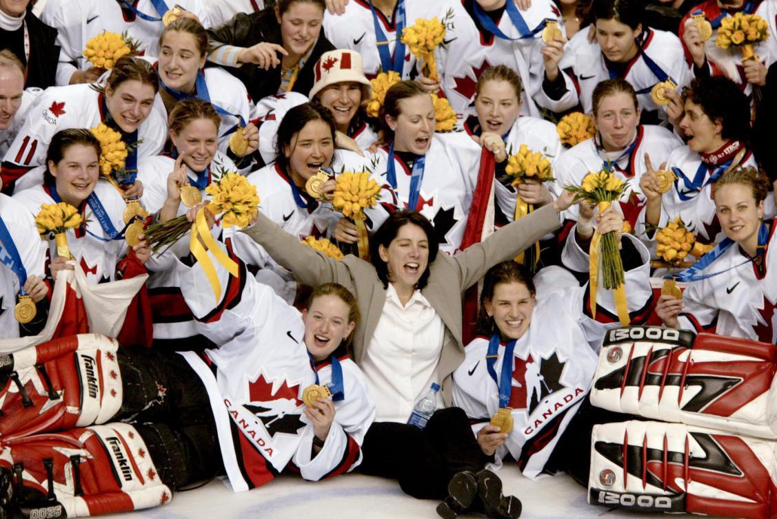 L'entraîneuse de l'équipe féminine canadienne de hockey Danièle Sauvageau (au centre) et son équipe arborant leur médaille d'or posent pour la photo de groupe après avoir battu les États-Unis avec un pointage de 3 -2, le jeudi 21 février 2002, aux Jeux olympiques d'hiver de Salt Lake City. (PHOTO PC/AOC/Mike Ridewood)