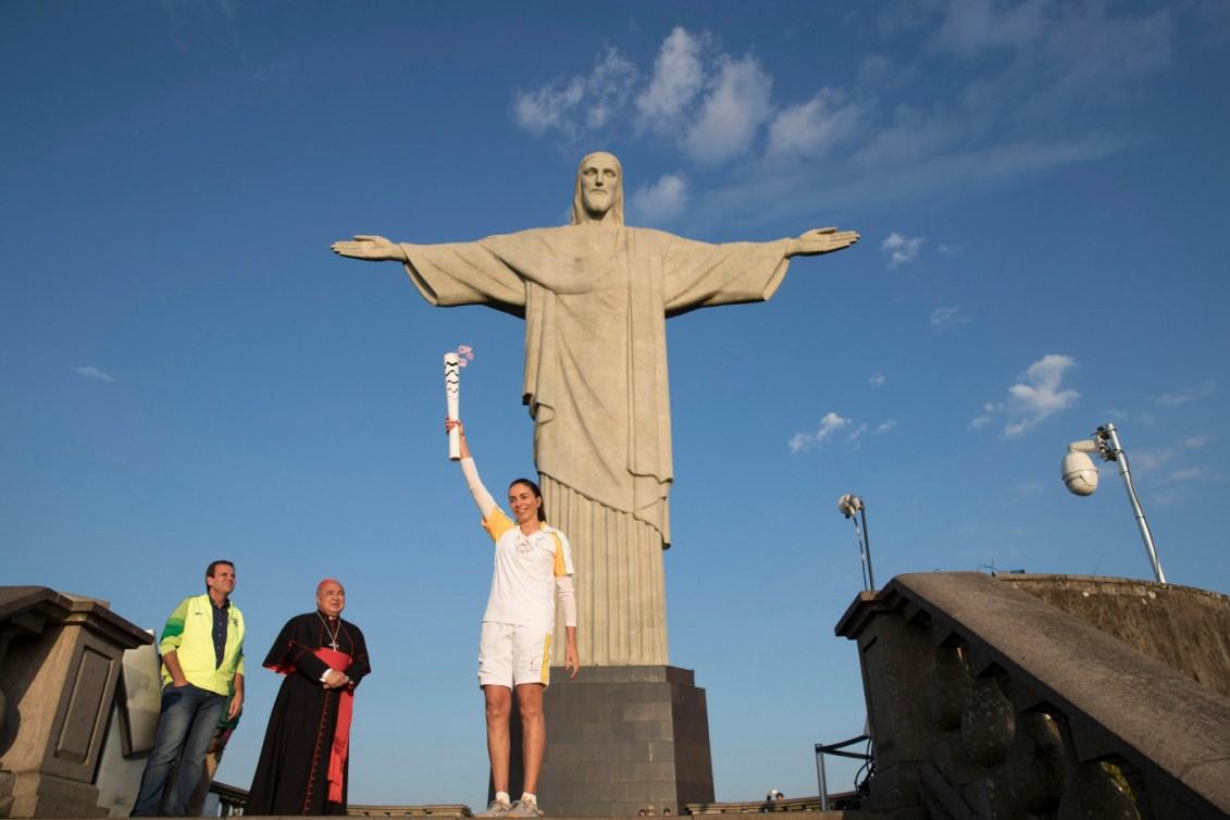 Une athlète brésilienne pose avec la flamme olympique devant le Chris Rédempteur.
