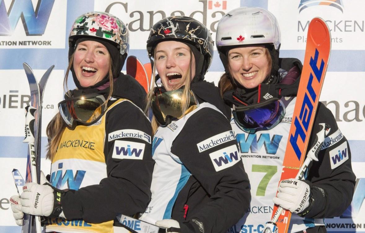 Chloé, Justine et Maxime Dufour-Lapointe posent sur un podium