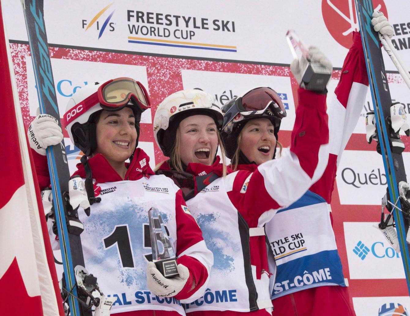 La skieuse acrobatique d'Équipe Canada Justine Dufour-Lapointe (centre) célèbre sa victoire à la Coupe du monde de Val St-Côme aux côtés de sa coéquipière Andi Naude (gauche) et sa soeur Chloé. (Photo : THE CANADIAN PRESS/Jacques Boissinot)