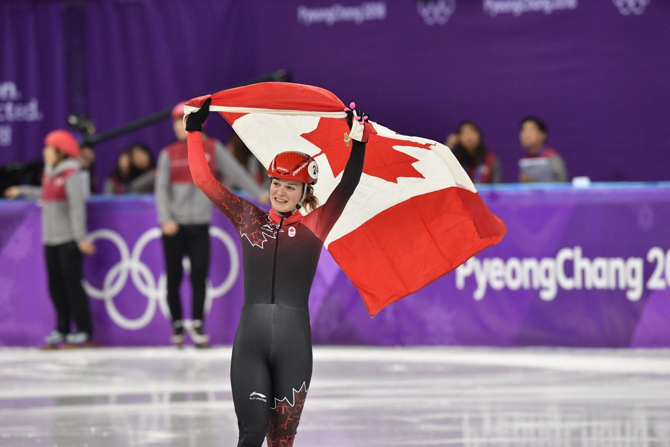 Kim Boutin d'Équipe Canada célèbre avec le drapeau canadien après avoir remoorté la médaille d'argent au 1000 m féminin en courte piste aux Jeux olympiques de PyeongChan, le 22 février 2018.