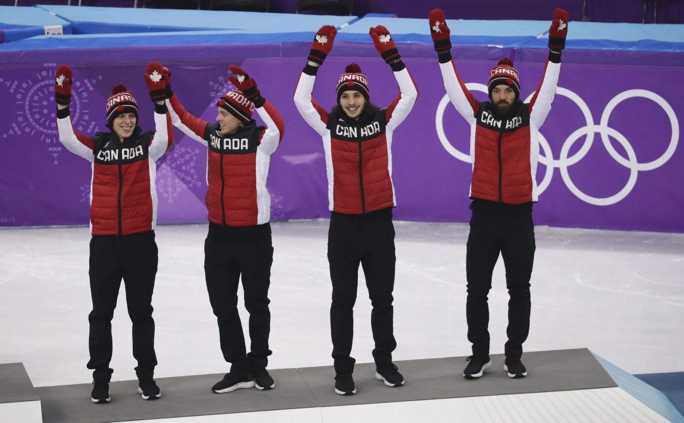 Charle Cournoyer, Pascal Dion, Samuel Girard et Charles Hamelin d'Équipe Canada célèbrent sur le podium après avoir remporté la médaille de bronze au relais 5000 m en courte piste aux Jeux olympiques de PyeongChang, en Corée du Sud, le 22 février 2018.