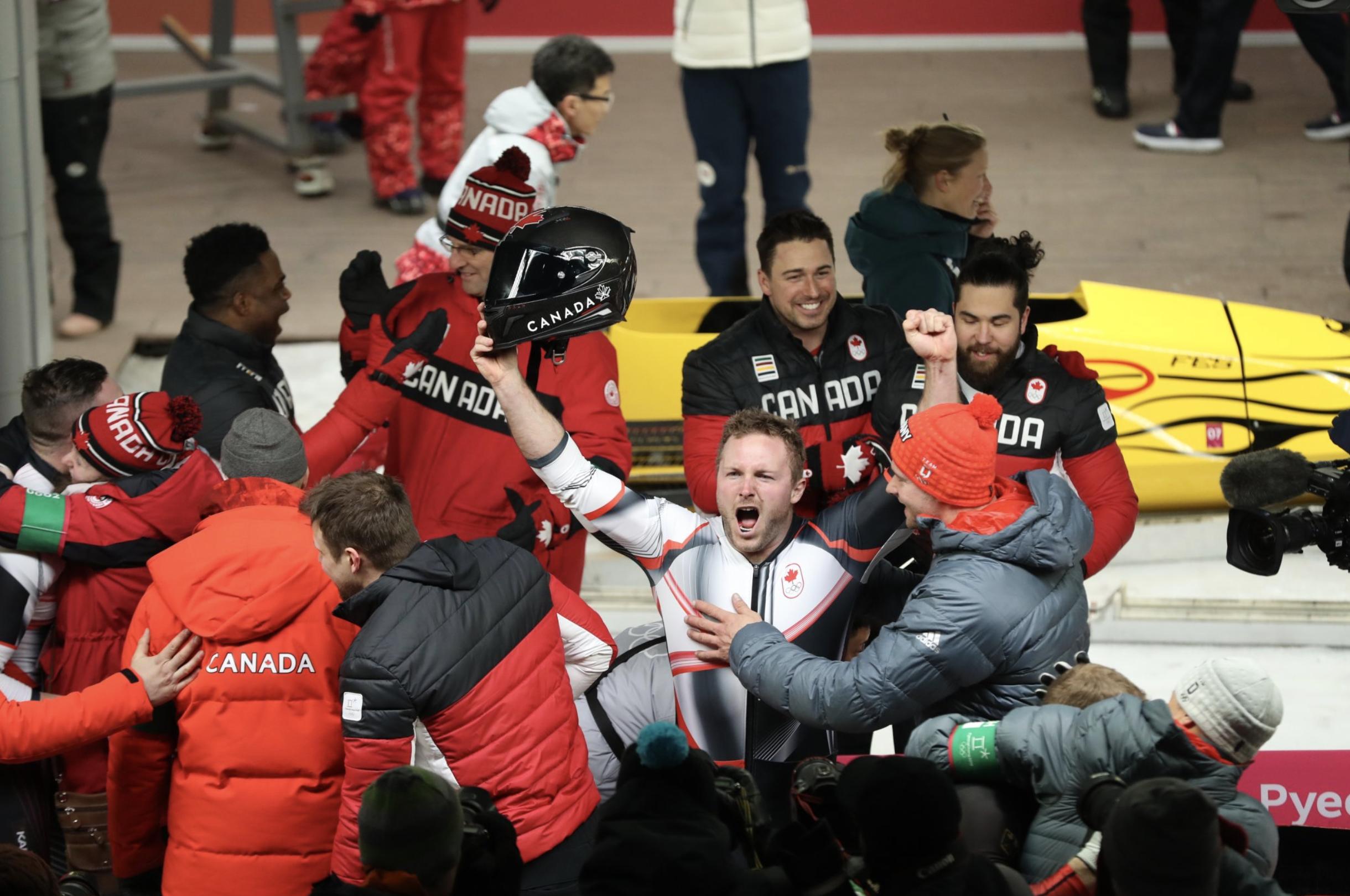 Justin Kripps d'Équipe Canada célèbre en compagnie de ses coéquipiers après avoir remporté la médaille d'or de l'épreuve masculine de bobsleigh à deux aux jeux olympiques de PyeongChang, le 19 février 2018.