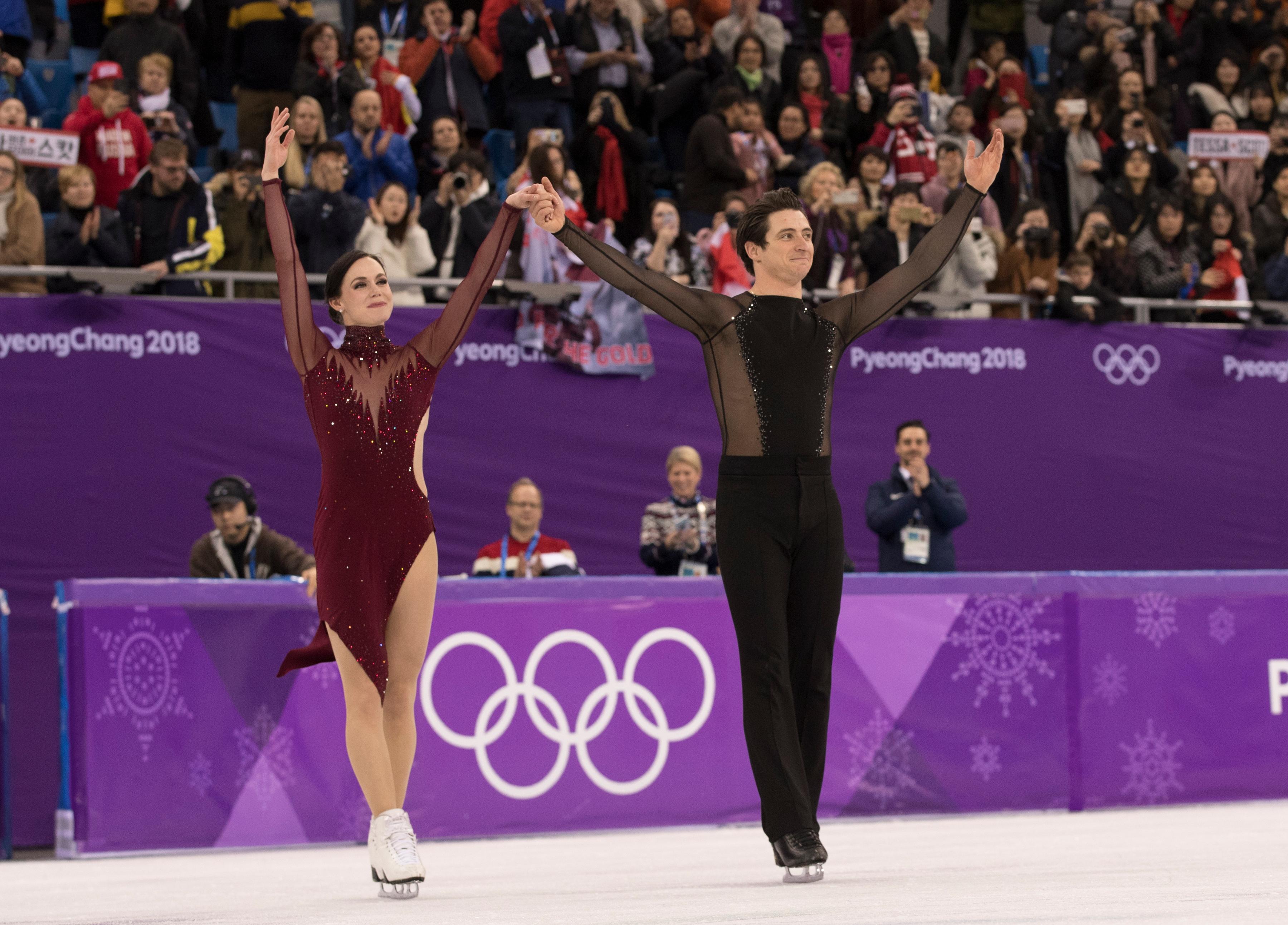 Tessa Virtue et Scott Moir d'Équipe Canada saluent la foule lors de la danse libre aux Jeux olympiques de PyeongChang, le 20 février 2018. (Photo : COC – Jason Ransom)