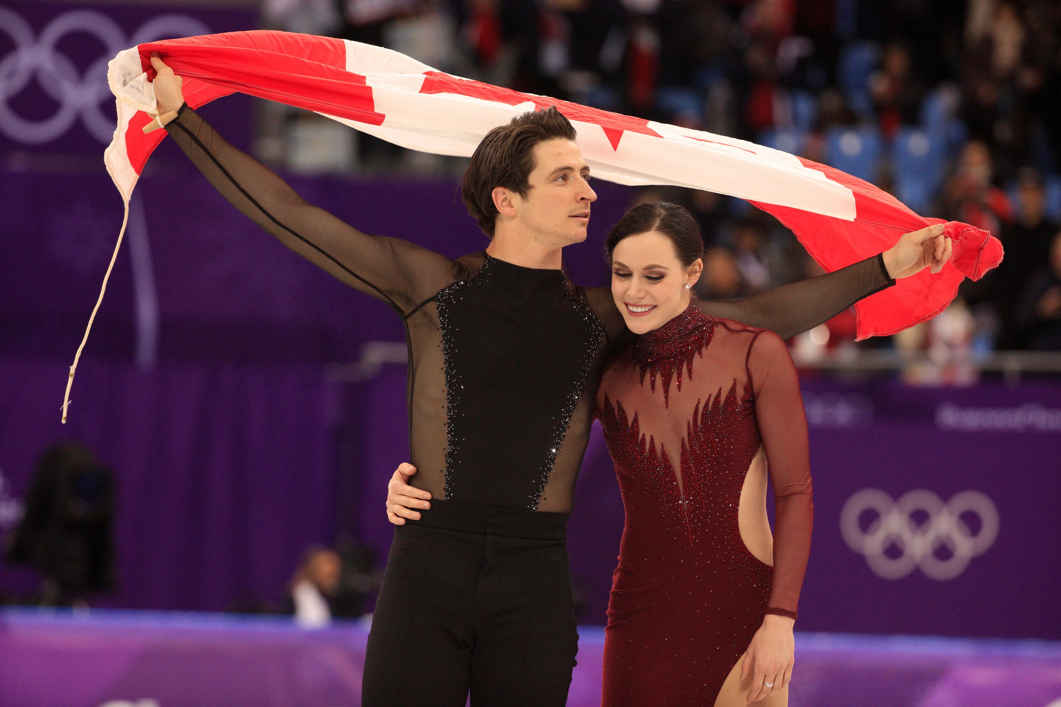 Tessa Virtue et Scott Moir effectuent un tour de piste avec le drapeau canadien après avoir décroché la médaille d'or en danse sur glace aux Jeux olympiques de PyeongChang, en Corée du Sud, le 20 février 2018.
