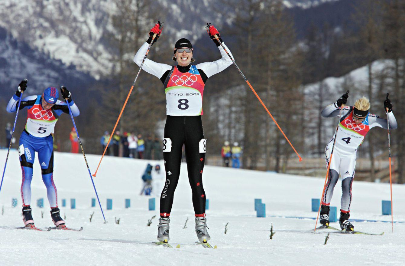 Chandra Crawford (8), de Canmore (Alberta), lève les bras pour célébrer tandis qu'elle franchit la ligne d'arrivée et remporte la médaille d'or à l'épreuve féminine de sprint en ski de fond aux Jeux olympiques de Turin 2006 à Pragelato Plan (Italie) le mercredi 22 février 2006. L'Allemande Claudia Kuenzel (4), médaillée d'argent, et la Russe Alena Sidko (5), médaillée de bronze, ne sont pas loin derrière. (PHOTO PC/Frank Gunn)