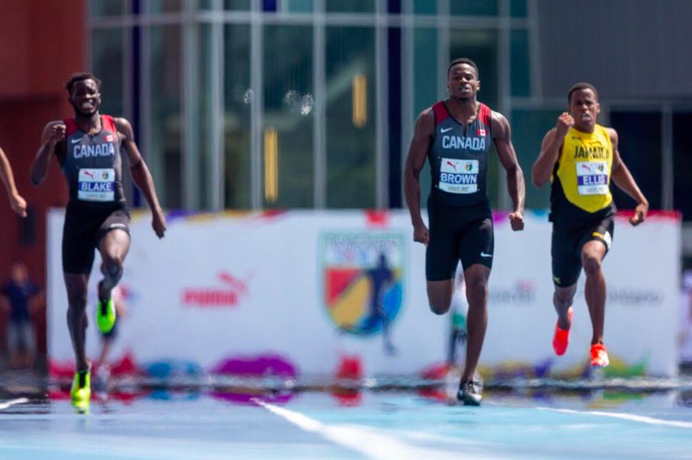Aaron Brown, au centre, lors de la finale du 200 m masculin aux Championnats NACAC de Toronto, le 12 août 2018. COC/Crystal Emmanuel porte le drapeau canadien après avoir remporté la médaille d'argent au 200 m, aux Championnats NACAC, à Toronto, le 12 août 2018. COC/Thomas Skrlj